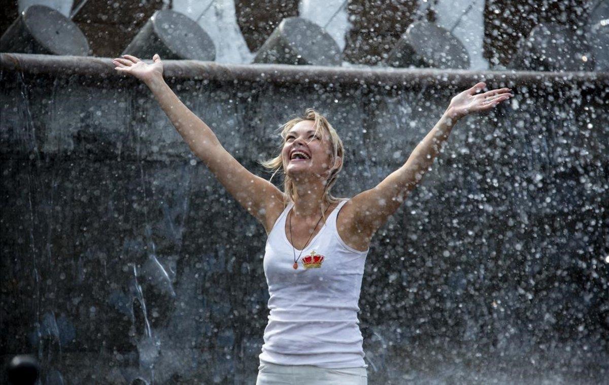 Una mujer se refresca en una fuente en el jardín de Alexander, cerca del Kremlin, en Moscú.