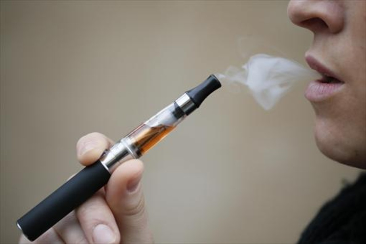 Una persona inhala vapor de un cigarrillo electrónico.