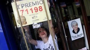 Una trabajadora de doña Manolita, en Madrid, coloca el número agraciado con el Gordo al lado del retrato de la fundadora de la histórica administración de Lotería.