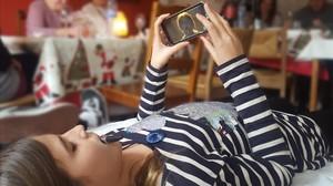 Una niña utilizando el teléfono móvil durante una comida familiar.