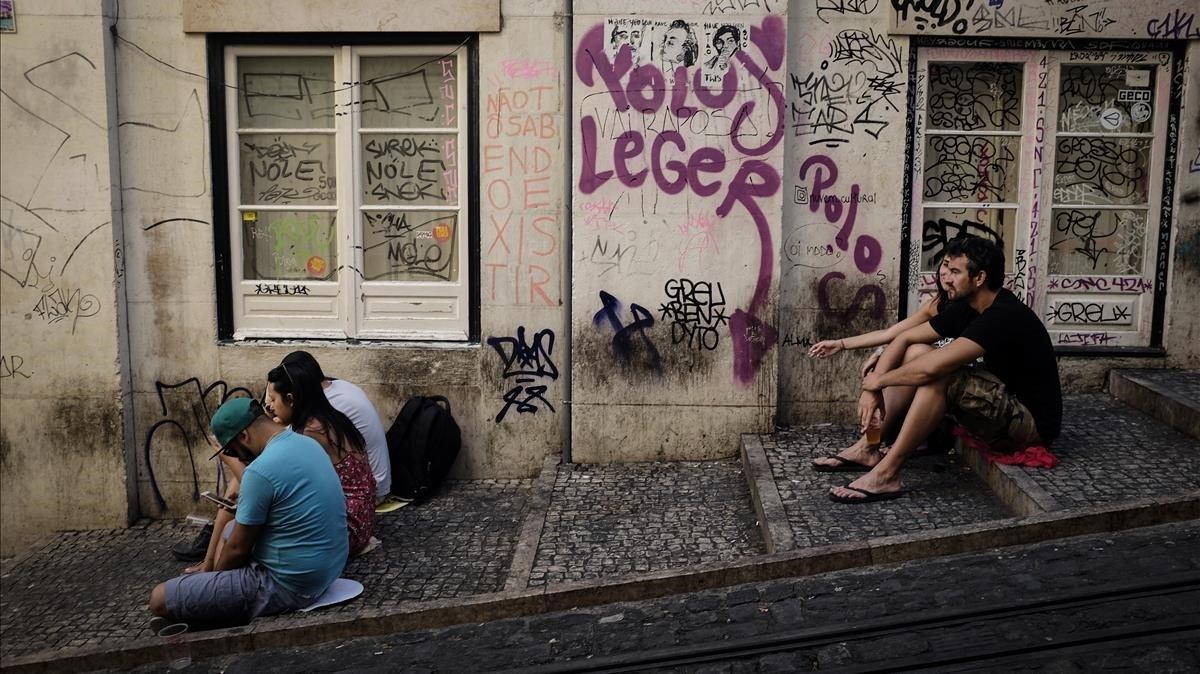Unos turistas esperan la llegada del tranvía en Lisboa.