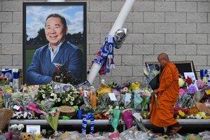 Un monje budista deja unas flores junto a la fotografía del empresario, a las afueras del estadio del Leicester.