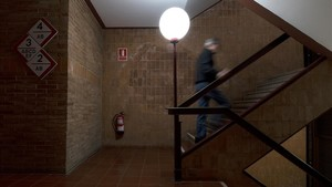 El interior de la Casa Fullà, con su señalética especial, sus suelos hidráulicos, sus paredes de ladrillo y una farola por lámpara.