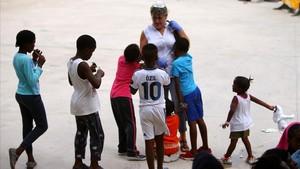 Una voluntaria juega con unos niños llegados en patera en el centro deportivo Antonio Gavira, en Algeciras.