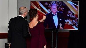 John Warhurst y Nina Hartstone siguen por televisión la entrega del Oscar a la mejor edición de sonido para John Warhurst, por 'Bohemian Rhapsody'.
