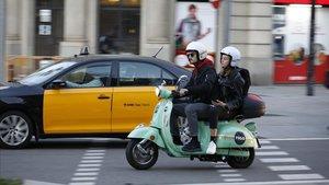 Una moto de movilidad compartida circulando por Barcelona.